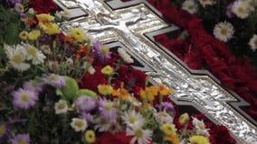 Ο ορθόδοξος σταυρός βρίσκεται στο βωμό στα λουλούδια απόθεμα βίντεο