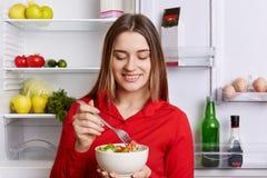 Ο οριζόντιος πυροβολισμός του εύθυμου θηλυκού κρατά το κύπελλο με τη σαλάτα φρέσκων λαχανικών, στέκεται κοντά friedge στο σύνολο  Στοκ Εικόνες