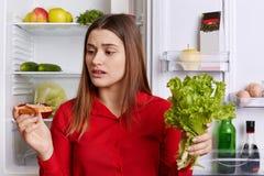 Ο οριζόντιος πυροβολισμός του θηλυκού brunette με την έκφραση εξετάζει το σάντουιτς, κρατά το μαρούλι, θέλει να φάει το κρέας, τη στοκ εικόνες