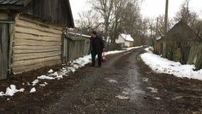 Ο ουκρανικός αγρότης με το ραβδί περπατήματος ελέγχει τη σιταποθήκη του όταν περίπατος έξω από το αγροτικό σπίτι του φιλμ μικρού μήκους