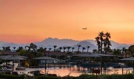 Ο ουρανός που χρωματίζεται με τα χρώματα του ήλιου, με τα βουνά στο υπόβαθρο, της σκιαγραφίας ενός αεροπλάνου που πετά στοκ εικόνα με δικαίωμα ελεύθερης χρήσης