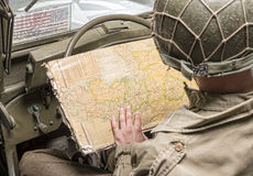 Ο οδηγός ενός στρατιωτικού οχήματος εξετάζει έναν χάρτη της Νορμανδίας Στοκ Εικόνες