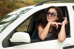 Ο οδηγός κοριτσιών μέσα στο πορτρέτο αυτοκινήτων, εξετάζει την απόσταση μέσω των γυαλιών ηλίου, θερινή περίοδο Στοκ Φωτογραφία