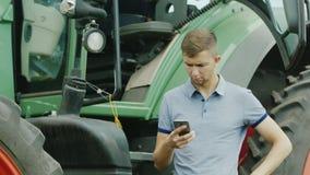 Ο οδηγός τρακτέρ χρησιμοποιεί ένα smartphone κοντά στο τρακτέρ του απόθεμα βίντεο