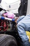 Ο οδηγός φορτηγού επιθεωρεί την όντας αναμμένη μηχανή του μεγάλου ημι φορτηγού Στοκ Φωτογραφία