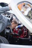 Ο οδηγός φορτηγού ελέγχει την ημι μηχανή φορτηγών εσωτερική κουκούλα Στοκ Φωτογραφίες