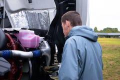 Ο οδηγός φορτηγού ελέγχει την ημι μηχανή φορτηγών πρίν οδηγεί το ημι φορτηγό Στοκ Φωτογραφίες