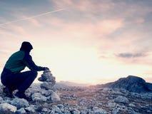 Ο οδοιπόρος ατόμων χτίζει την πυραμίδα χαλικιών Πέτρες στην κορυφή βουνών Άλπεων Ορίζοντας χαραυγών Στοκ Φωτογραφίες