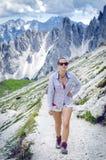 Ο οδοιπόρος γυναικών βρίσκεται έχει ένα υπόλοιπο βουνά Αιχμές όπως ένα υπόβαθρο ημέρα ηλιόλουστη οδοιπορία Φλόγα φακών Το επιτυχέ Στοκ Φωτογραφία