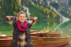 Ο οδοιπόρος γυναικών με τα χέρια πίσω από το κεφάλι της χαλαρώνει στη λίμνη Bries στοκ φωτογραφία