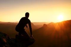 Ο οδοιπόρος παίρνει τη χαλάρωση σε έναν βράχο και την απόλαυση του ηλιοβασιλέματος στον ορίζοντα Ζωηρή επίδραση Στοκ Φωτογραφίες