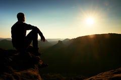 Ο οδοιπόρος παίρνει τη χαλάρωση σε έναν βράχο και την απόλαυση του ηλιοβασιλέματος στον ορίζοντα Ζωηρή επίδραση Στοκ Εικόνες