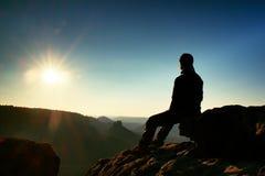 Ο οδοιπόρος παίρνει τη χαλάρωση σε έναν βράχο και την απόλαυση του ηλιοβασιλέματος στον ορίζοντα Ζωηρή επίδραση Στοκ Εικόνα