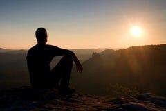 Ο οδοιπόρος παίρνει τη χαλάρωση σε έναν βράχο και την απόλαυση του ηλιοβασιλέματος στον ορίζοντα Ζωηρή επίδραση Στοκ εικόνες με δικαίωμα ελεύθερης χρήσης