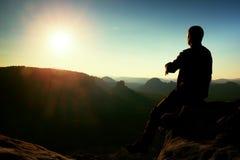 Ο οδοιπόρος παίρνει τη χαλάρωση σε έναν βράχο και την απόλαυση του ηλιοβασιλέματος στον ορίζοντα Ζωηρή επίδραση Στοκ Φωτογραφία
