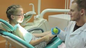 Ο οδοντίατρος δίνει στο μικρό κορίτσι ένα πράσινο μήλο απόθεμα βίντεο