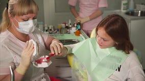 Ο οδοντίατρος γιατρών διδάσκει τον έφηβο για να βουρτσίσει τα δόντια του στο παράδειγμα ενός ομοιώματος απόθεμα βίντεο