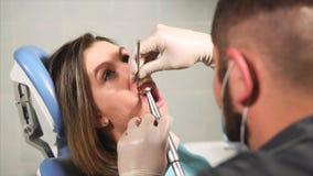 Ο οδοντίατρος γιατρών καθαρίζει τα δόντια για τη νέα γυναίκα από την πινακίδα και τον τάρταρο απόθεμα βίντεο