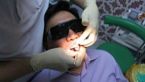 Ο οδοντίατρος θεραπεύει τα δόντια πελατών με το στοματικό καθρέφτη απόθεμα βίντεο