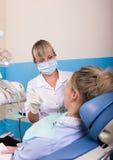 Ο οδοντίατρος θεραπεύει τον ασθενή δοντιών Στοκ Εικόνες