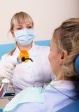 Ο οδοντίατρος θεραπεύει τον ασθενή δοντιών Στοκ Φωτογραφία