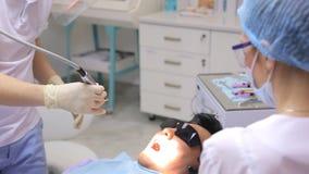 Ο οδοντίατρος κάνει τη λεύκανση δοντιών ή άλλη συνηθισμένη λειτουργία στο στόμα χρησιμοποιώντας τον οδοντικά εξοπλισμό ή τα όργαν απόθεμα βίντεο