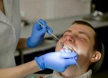 Ο οδοντίατρος κάνει τις διαδικασίες επεξεργασίας στο οδοντικό γραφείο Στοκ Εικόνες