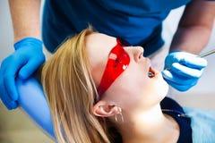 Ο οδοντίατρος μεταχειρίζεται τα δόντια Στοκ Εικόνα