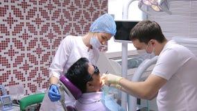 Ο οδοντίατρος παίρνει την αρχική εξέταση του ασθενή, άτομα καρέκλα, που βοηθιούνται στην οδοντική από μια νοσοκόμα φιλμ μικρού μήκους