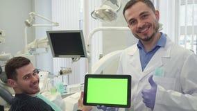Ο οδοντίατρος παρουσιάζει αντίχειρά του στο γραφείο του απόθεμα βίντεο
