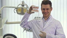 Ο οδοντίατρος παρουσιάζει αντίχειρά του στο γραφείο απόθεμα βίντεο