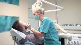 Ο οδοντίατρος που εξετάζει τα υπομονετικά δόντια ` s, τον εξηγεί διαδικασία φιλμ μικρού μήκους