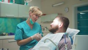 Ο οδοντίατρος που εξετάζει τα υπομονετικά δόντια ` s, τον εξηγεί διαδικασία Ο πυροβολισμός ολισθαινόντων ρυθμιστών, έφυγε απόθεμα βίντεο