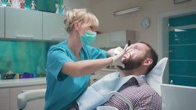 Ο οδοντίατρος που εξετάζει τα υπομονετικά δόντια ` s, τον εξηγεί διαδικασία steadicam φιλμ μικρού μήκους