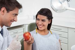 Ο οδοντίατρος που παρουσιάζει αντίχειρες υπογράφει επάνω σε έναν θηλυκό ασθενή Στοκ φωτογραφία με δικαίωμα ελεύθερης χρήσης
