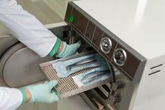 Ο οδοντίατρος τοποθετεί την ιατρική χύτρα πιέσεως για την αποστείρωση χειρουργική στοκ εικόνα