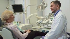 Ο οδοντίατρος χαιρετά το θηλυκό πελάτη στο γραφείο του απόθεμα βίντεο