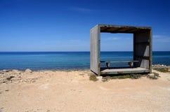 Ο πάγκος μέσα στο ξύλινο πλαίσιο, χαλαρώνει τη θέση στην παραλία της Κύπρου, παραλία Pahos Στοκ εικόνα με δικαίωμα ελεύθερης χρήσης