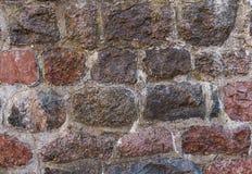 Ο πέτρινος τοίχος ξεπέρασε το ψημένο κομμάτι κυβόλινθων σύστασης ανώμαλο του παλαιού υποβάθρου κατασκευής Στοκ εικόνες με δικαίωμα ελεύθερης χρήσης