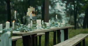Ο πίνακας εξυπηρέτησε για το ρομαντικό γεύμα με ομιχλώδεις δασικές θαυμάσιες λεπτομέρειες του ντεκόρ: φύλλα, λουλούδια, κεριά και απόθεμα βίντεο