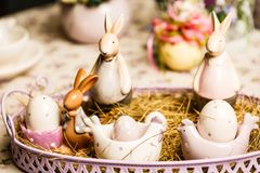 Ο πίνακας προγευμάτων Πάσχας με το τσάι, αυγά στα φλυτζάνια αυγών, άνοιξη ανθίζει στο βάζο και το ντεκόρ Πάσχας Στοκ εικόνα με δικαίωμα ελεύθερης χρήσης