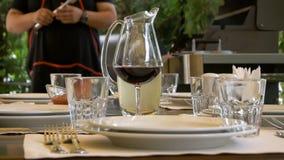 Ο πίνακας στο εστιατόριο χρησιμεύεται για να συναντήσει τους φιλοξενουμένους Ένα ποτήρι του κόκκινου κρασιού συγχωνεύει με την κα απόθεμα βίντεο