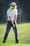 Ο παίκτης γκολφ πελεκά μια σφαίρα γκολφ επάνω στο πράσινο με το γκολφ γ οδηγών Στοκ Εικόνες