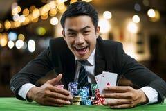 Ο παίκτης πόκερ που παρουσιάζει ένα ζευγάρι των κόκκινων άσσων και της λαβής στοιχημάτισε ένα larg στοκ φωτογραφίες