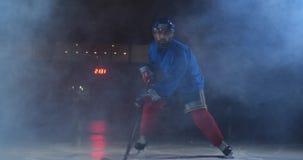Ο παίκτης χόκεϋ ατόμων με μια σφαίρα στο χώρο πάγου παρουσιάζει την κίνηση ροής άμεσα προς τη κάμερα και να φανεί ευθύς απόθεμα βίντεο