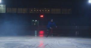 Ο παίκτης χόκεϋ ατόμων με μια σφαίρα στο χώρο πάγου παρουσιάζει την κίνηση ροής άμεσα προς τη κάμερα και να φανεί ευθύς φιλμ μικρού μήκους