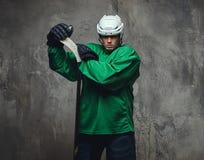 Ο παίκτης χόκεϋ που φορούν το πράσινο προστατευτικό εργαλείο και το λευκό κράνος που στέκεται με το χόκεϋ κολλούν σε ένα γκρίζο υ Στοκ Εικόνες