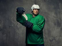 Ο παίκτης χόκεϋ που φορούν το πράσινο προστατευτικό εργαλείο και το λευκό κράνος που στέκεται με το χόκεϋ κολλούν σε ένα γκρίζο υ Στοκ φωτογραφία με δικαίωμα ελεύθερης χρήσης