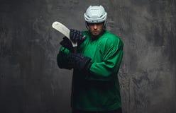 Ο παίκτης χόκεϋ που φορούν το πράσινο προστατευτικό εργαλείο και το λευκό κράνος που στέκεται με το χόκεϋ κολλούν σε ένα γκρίζο υ Στοκ Εικόνα