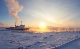 Ο παγοθραύστης σπάζει τον πάγο στο ηλιοβασίλεμα Στοκ Φωτογραφίες